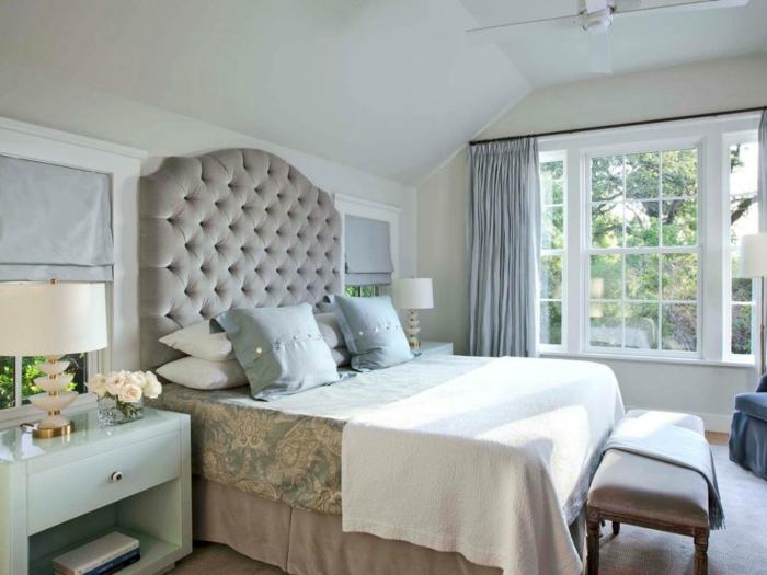 une chambre vintage coquette, tête de lit capitonnée, banquette de lit grise, grande fenêtre blanche