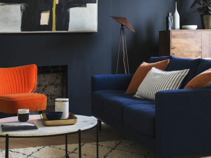 aménagement salon moderne, table basse ovale, tapis berbère, fauteuil orange, canapé bleu deux places, décoration intérieure salon