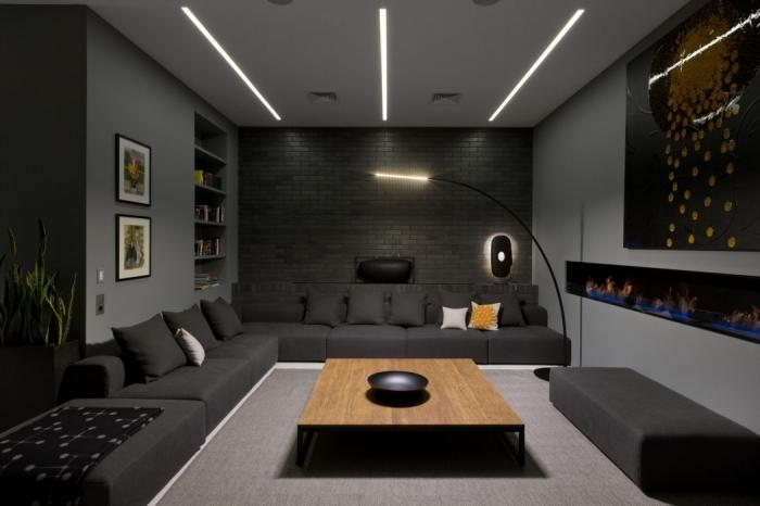 design intérieur en couleurs foncés dans l'esprit moderne avec un plafond blanc à éclairage neon blanc et pan de mur en pierre