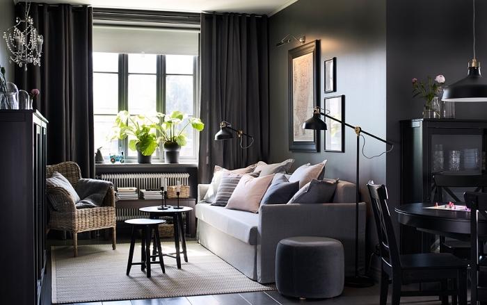 aménagement de salon aux murs foncés avec canapé gris clair couvert de coussins en couleurs pastel et meubles de bois peint noir