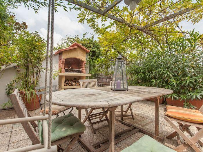 exemple de cheminée extérieure style campagne, chaises et table bois brut pour aménager un coin repos salle à manger en plein air