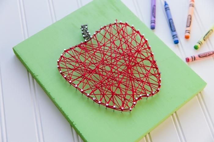 idée pour activite enfant facile et amusante avec une planche de bois peinte en vert et une pomme en fil rouge