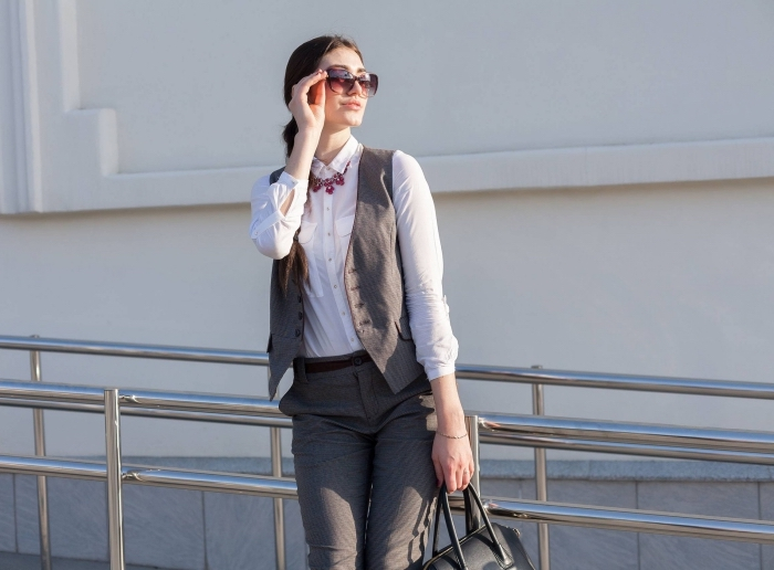 modèle de tailleur femme chic avec pantalon et gilet sans manches de couleur gris clair combiné avec ceinture noire et chemise blanche