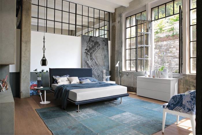 exemple de décoration industrielle dans la chambre à coucher avec verriere industrielle, linge de lit bleu et blanc, tapis bleu, sok en parquet marron, murs à effet béton