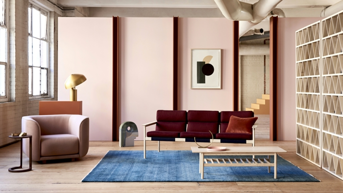 table basse bois, tapis bleu rectangulaire, fauteuil taupe, mur rose pastel