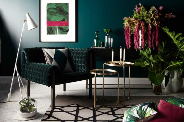 décoration intérieure salon en couleurs tendance, mur bleu canard, tapis blanc aux motifs noirs, plantes vertes, tableau art, petites tables gigognes