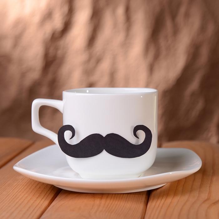 exemple de cadeau fete des peres personnalisé avec une tasse de café blanche décorée de moustaches noirs