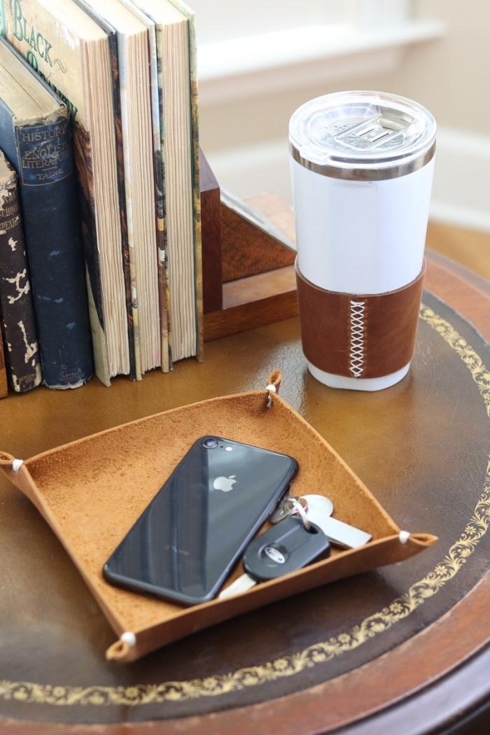 exemple rangement objets utile avec un support marron pour portable et clés sur une petite table ronde et foncée