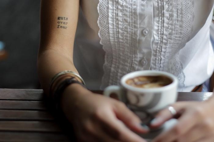 idée tatouage discret avec mots inspirants en lettres minuscules sur la main, modèle de chemise blanche avec dentelle et manches courtes