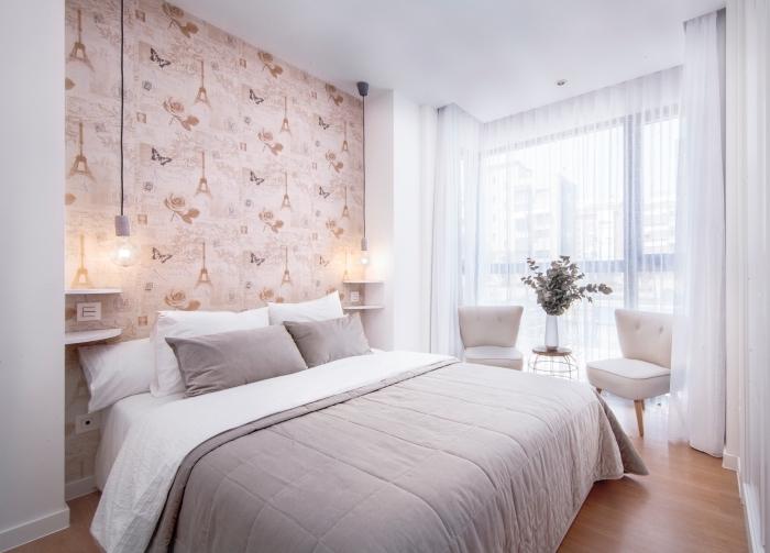 une chambre à coucher au décor doux et épuré avec une niche murale tapissée de papier peint tete de lit à motif tour eiffel