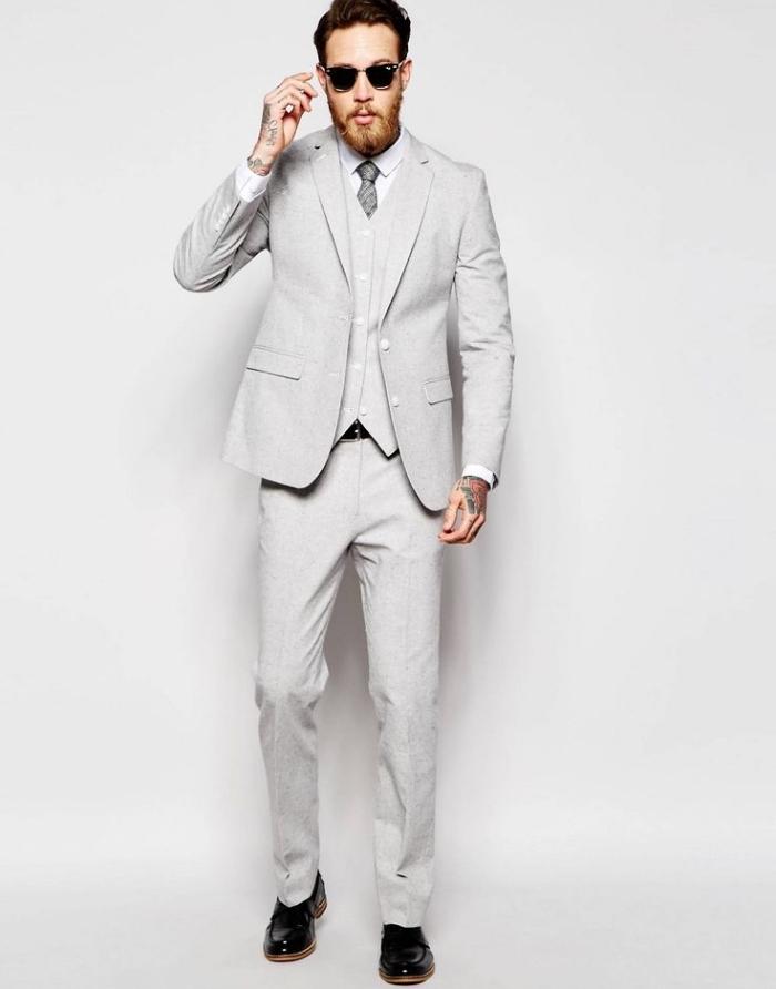un costume homme pas cher de la marque assos, trois pièces en gris clair rehaussé par une cravate en gris plus foncé et des chaussures cuir verni noir