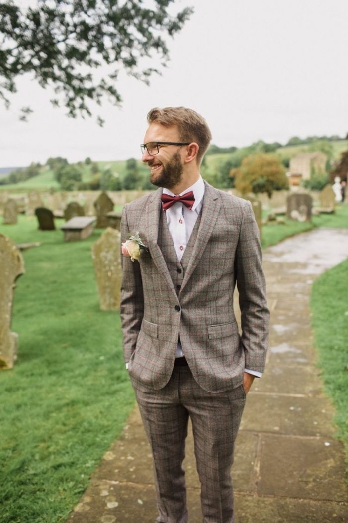 silhouette élégante en costume de marié en tweed à carreaux composé de trois pièces, assorti avec un noeud papillon couleur bordeaux, tenue champetre homme pour un mariage à thème rustique