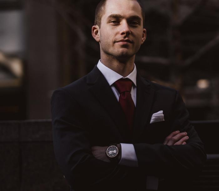 exemple de style vestimentaire homme élégant habillé en veston noir et chemise blanche accessoirisés avec cravate rouge foncé et montre noir or