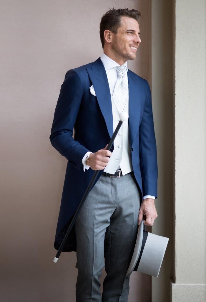 un modèle de redingote homme dépareillée avec pantalon gris, une veste bleu marine profond, gilet blanc et lavalière vintage