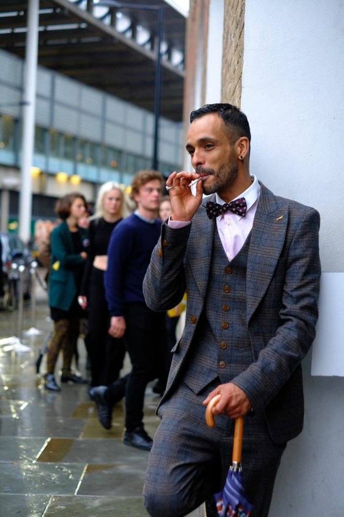 homme en costume tweed qui fume, tenue homme chic, appuyé sur son parapluie en bleu et blanc, gilet en tweed, chemise rose, papillon noir aux pois rouges