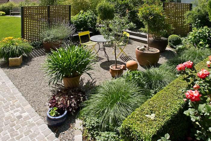 chemin de pavage exterieur, terrasse recouverte de gravier, plantes en pots, bordure de buis, chaise et tables metalliques, treillis occulants