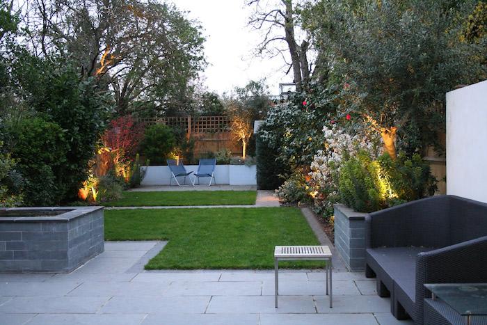 dalles de béton et carrés de gazon sur une terrasse exterieure, chaises metalliques, bordure de végétaux, canapé noir