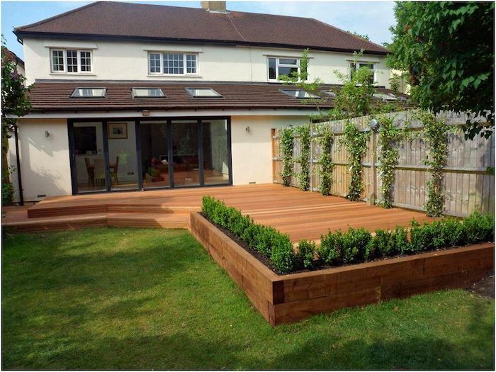 terrasse en bois composite exterieure, bordée de buis plantés et d une palissade envahie par lierre