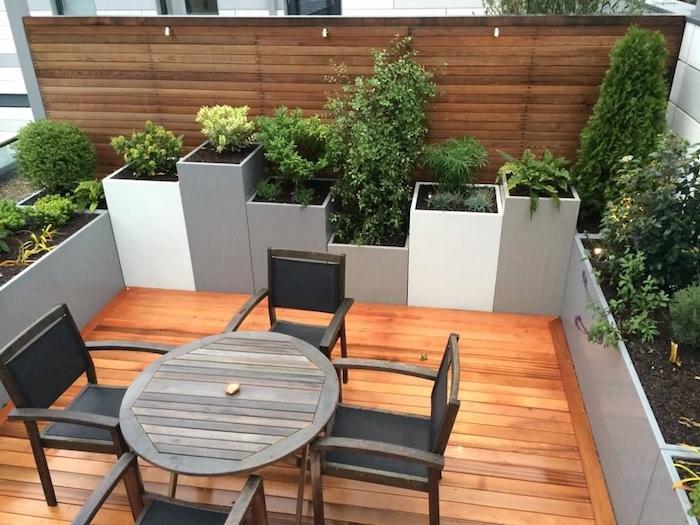 modele de terrasse bois composite claire avec table et chaises bois entourées de bacs à fleurs en bordure