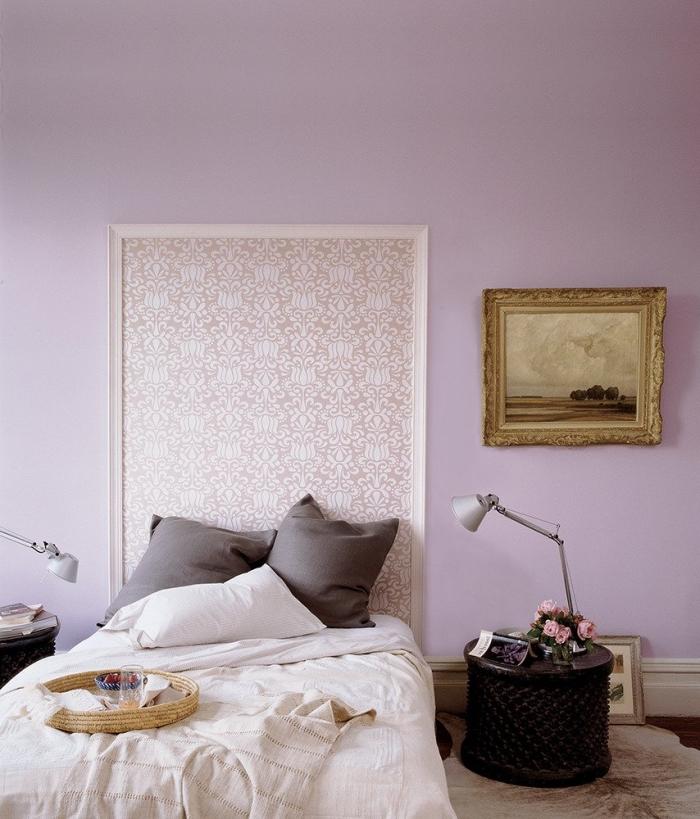 du papier peint encadré à motif vintage qui fait office d'une tête de lit originale, une tete de lit papier peint beige doré en harmonie avec la chambre à coucher couleur lavande
