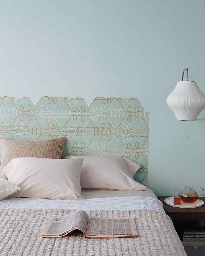 une tete de lit diy réalisée en papier peint imprimé motif vintage, découpée dans une forme imitant la structure d'une tête de lit en bois