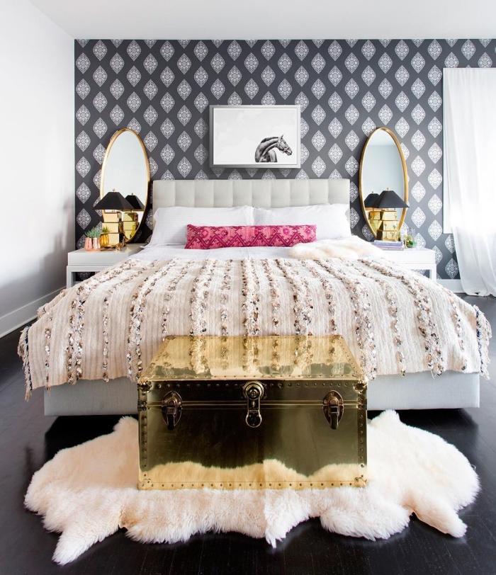 le papier peint tete de lit graphique en noir et gris s'harmonise parfaitement avec les accents dorés et la parure de lit