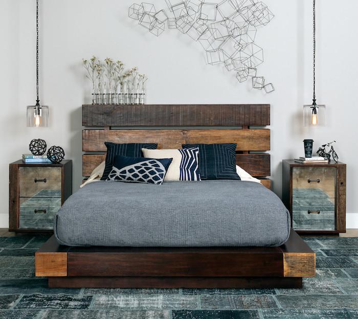 tête de lit en palette de bois, matelas gris sur plate forme bois, tapis gris, table de nuit bois et métal. déco murale composition métallique