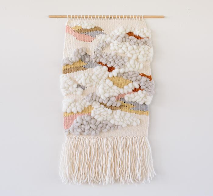 tissage laine modele macramé avec laine tissée beige et reliefs sur mur blanc