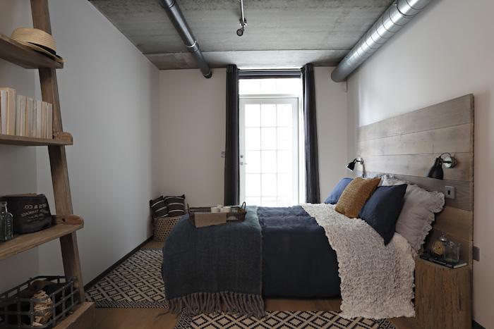 tuyauterie industrielle, murs blancs, echelle decorative bois, linge de lit blanc et bleu, tapis à figurines blanches et noires, tête de lit bois