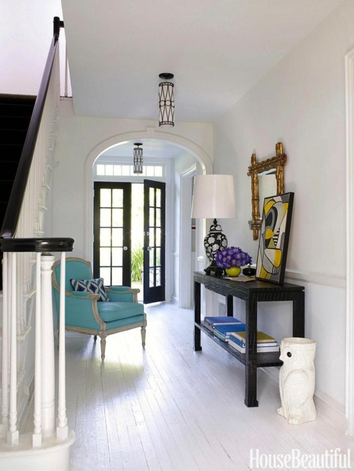 couloir blanc, table noire, peinture abstraite en gris et jaune, fauteuil bleu