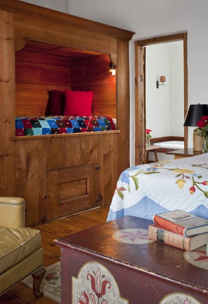 déco chambre fille ado, niche relax en bois en forme de cube, vieille malle de rangement en marron avec effet vieilli, grand fauteuil en cuir couleur moutarde, couverture de lit motifs fleuris en blanc et bleu