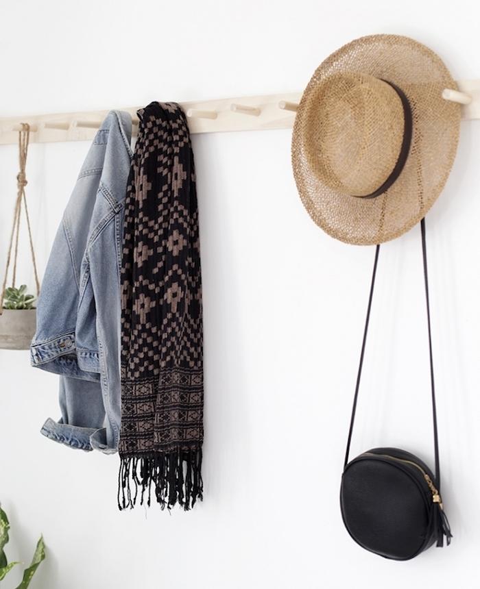 latte de bois clair avec des chevilles plantées dedans sur un mur blanc, porte manteau mural original pour accrocher vetements et accessoires