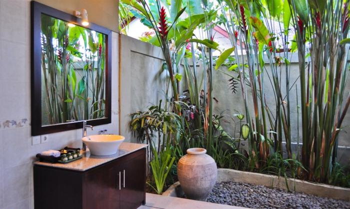 salle de bain verte, grand miroir au cadre noir, meuble en marron foncé, plantes exotiques de taille haute, plantes vertes d'intérieur