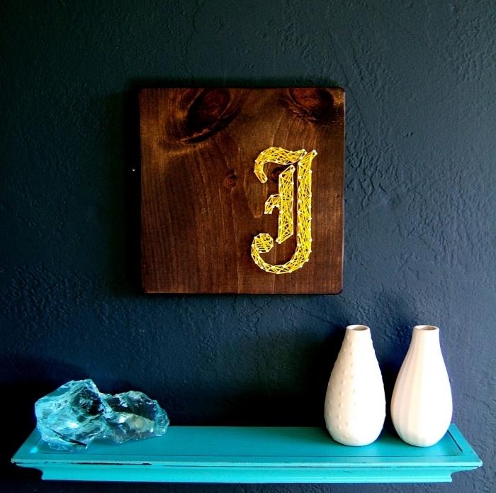 modèle de tableau fil tendu de bois foncé en forme carré avec initiale en fil jaune et clous, design intérieur aux murs foncés avec étagère turquoise