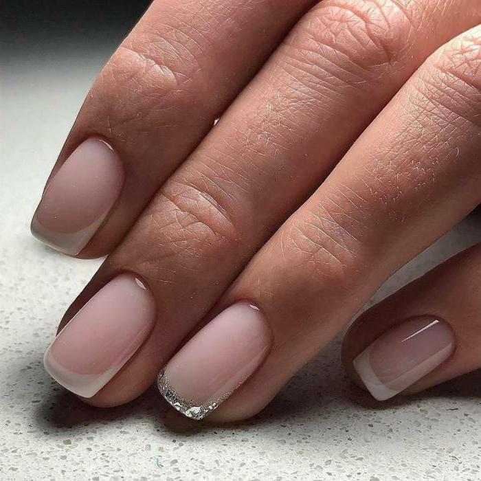 french manucure avec du blanc aux bouts, paillettes argentées au bout de l'un des doigts