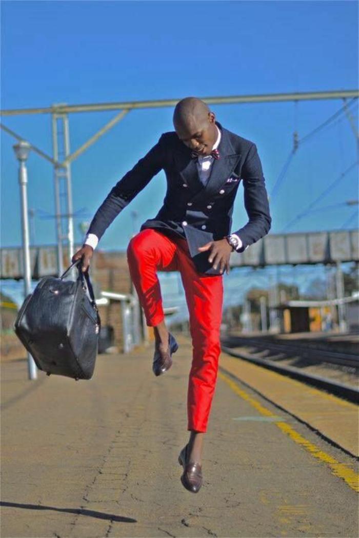 marque vetement homme tendance, monsieur qui fait un grand saut de joie, pantalon rouge, veste bleu marine type capitaine de bateau, chaussures pointues couleur taupe, grand sac noir de voyages