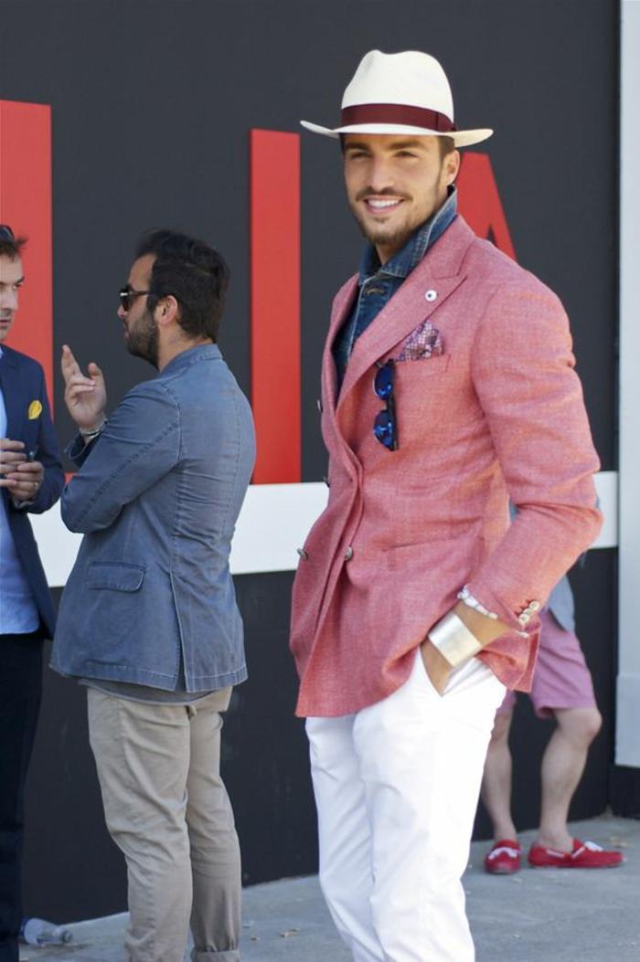 vetement homme stylé, veste rose saumon, pantalon blanc, chemise bleue en denim, borsalino blanc, lunettes de soleil avec des verres blancs