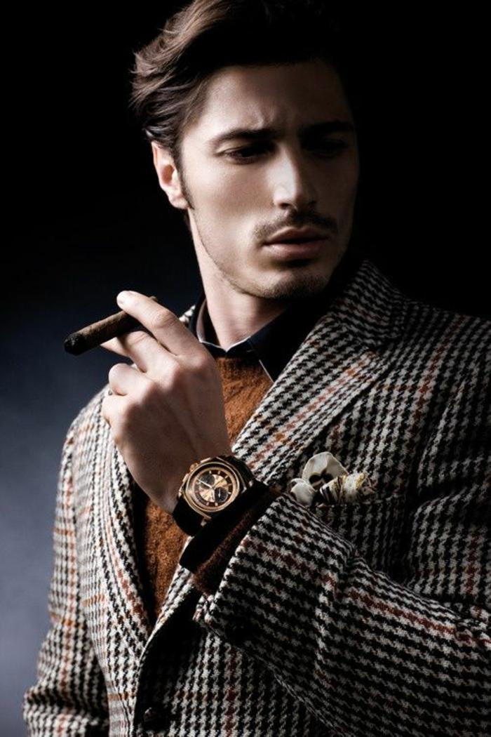veste a carreaux marrons et beiges, pull en marron clair, montre cadran rond doré au bracelet noir, tenue homme chic, homme qui fume un cigare, look de luxe