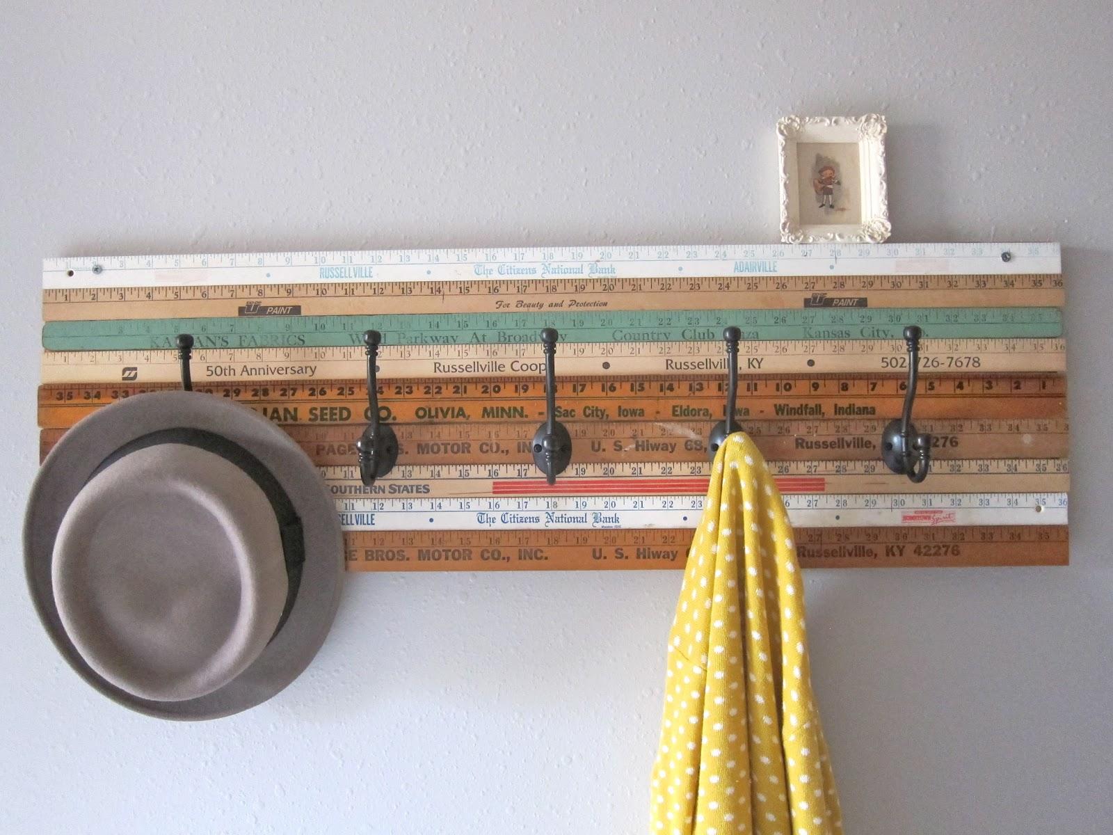 des règles vintage assemblées avec des accroches noires metalliques sur un mur blanc, rangement vetements et accessoires