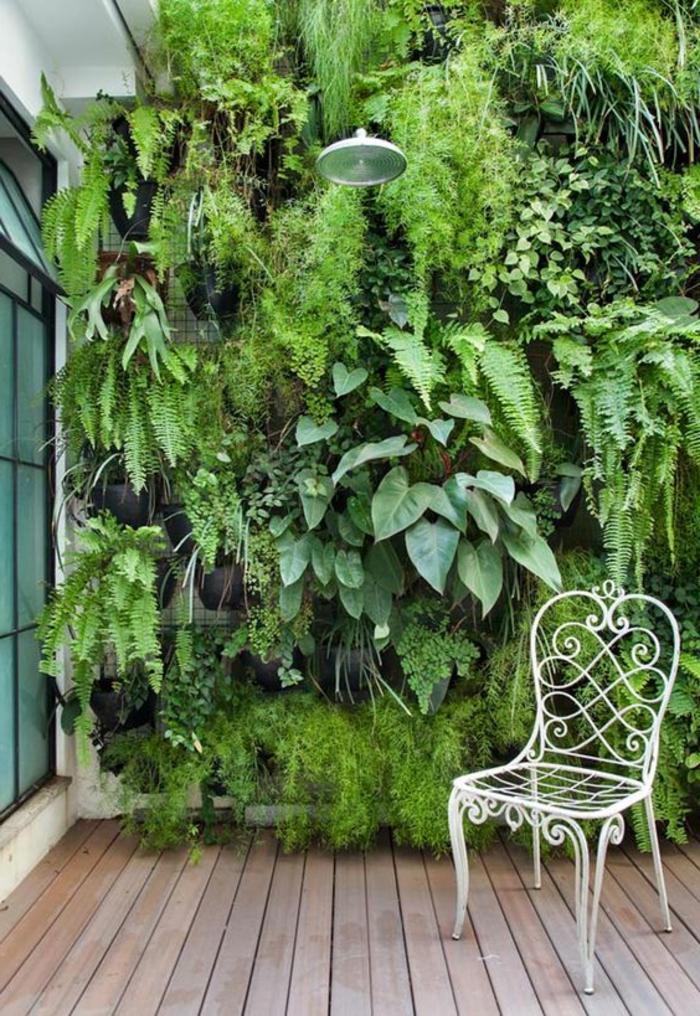 un grand mur végétal très vert, zone douche extérieure, chaise en métal blanc en style rétro, sol recouvert de poutres en bois marron clair, habiller un mur extéieur