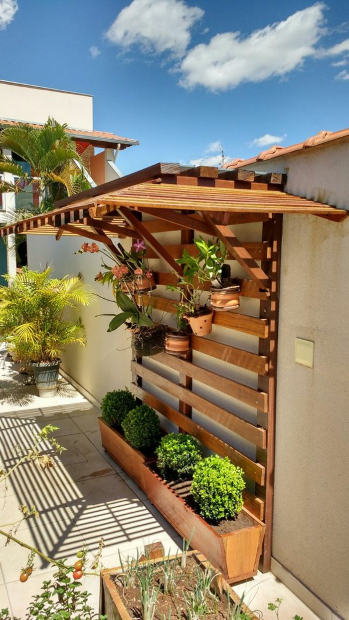 deco mur exterieur, coin pour un porte-plante original en bois beige, petit toit installé au-dessus des plantes, mur de jardin peint en couleur ivoire