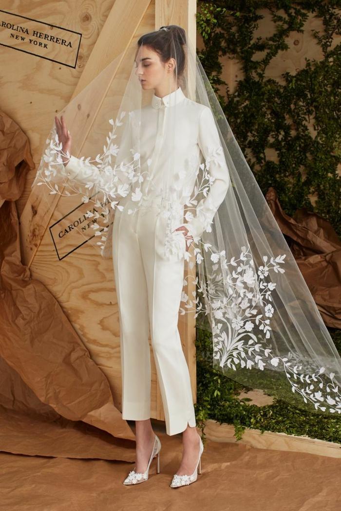 tenue ceremonie femme avec un long voile transparent avec de la dentelle blanches sur les ourlets aux motifs fleurs et feuilles, pantalon cigarette avec des fentes latérales aux chevilles