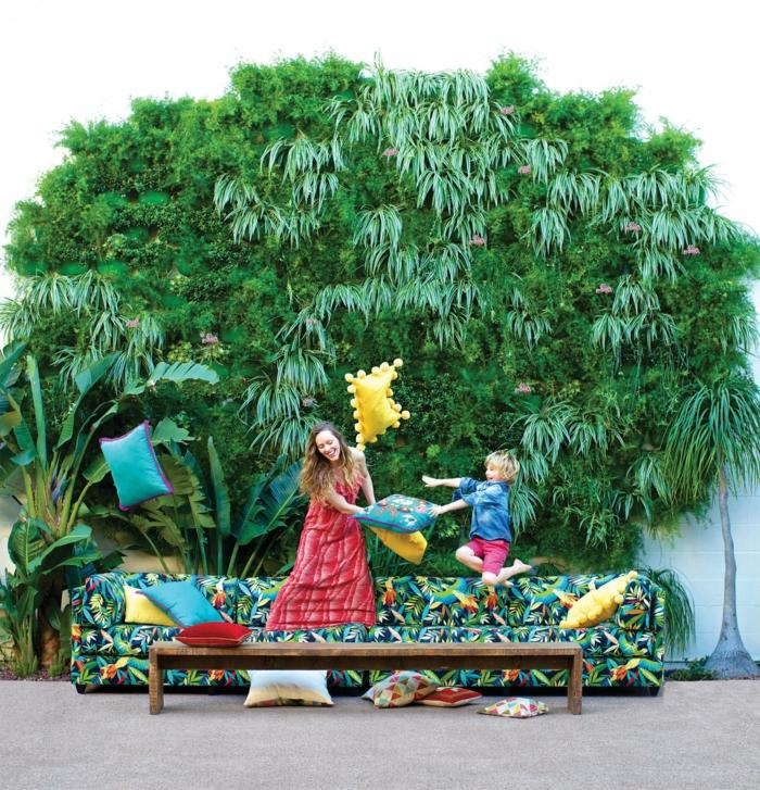 mur vegetal en palette, mur végétalisé, cloison végétale, mur en bleu pastel couvert de plantes de type palmier, canapé en noir, vert et jaune