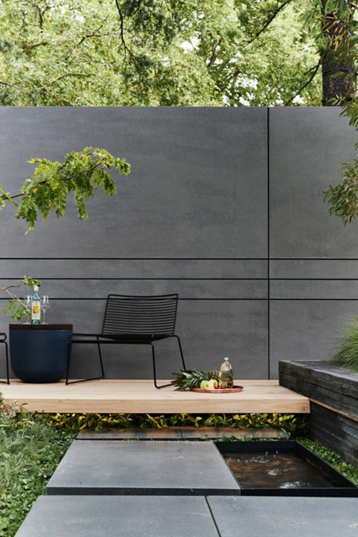 deco mur exterieur en gris anthracite avec des lignes graphiques sur sa largeur, fauteuil en métal noir, table en rotin noire, revetement du sol en bois clair