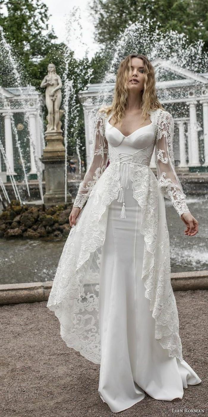 un modèle de Lian Rokman, robe avec bustier en satin blanc, dentelle blanche, robe sirene mariage, style Renaissance, deux pompons blancs devant