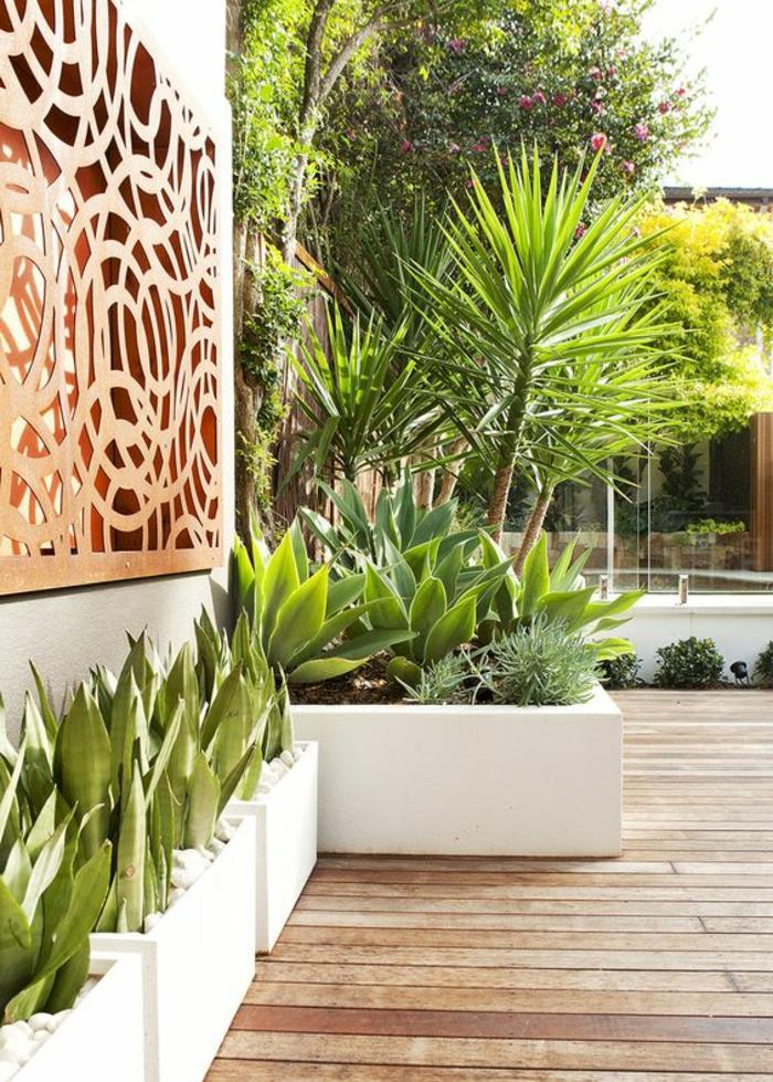 revetement mur exterieur, comment habiller un mur exterieur avec un panneau en bois ajouré, mur en blanc, coin de jardin décoré de grands pots blancs rectangulaires avec des plantes exotiques