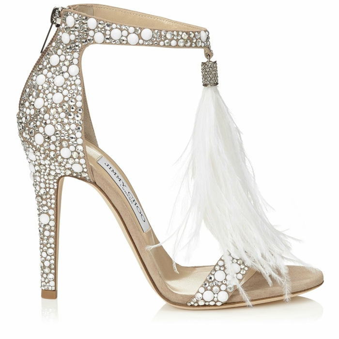 modèle de Jimmy Choo, chaussure blanche mariage, gros pompons en plumes d'autruche devant, talons aiguilles hauts, surface recouverte de petites perles en plastique blanches, chaussure mariee