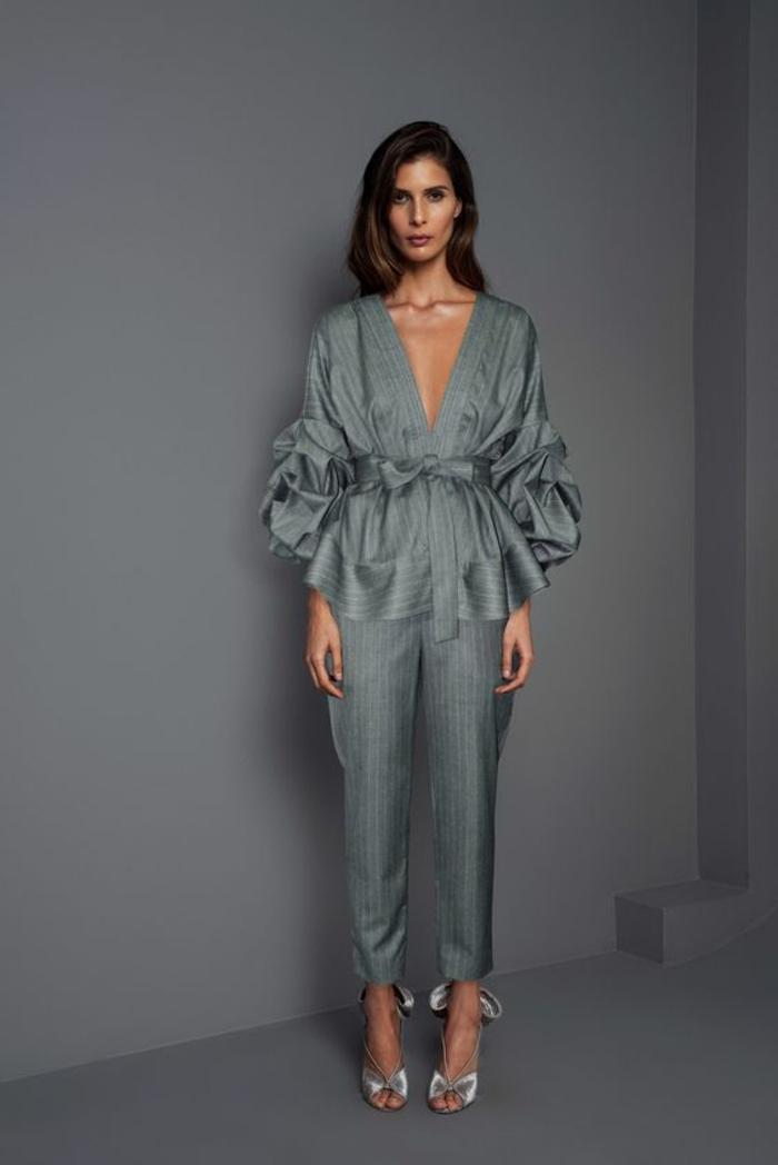 tenue ceremonie femme en gris satiné, blouse avec le col profond en V avec les manches bouffantes aux effets drapés aux coudes, pantalon type cigarette fluide
