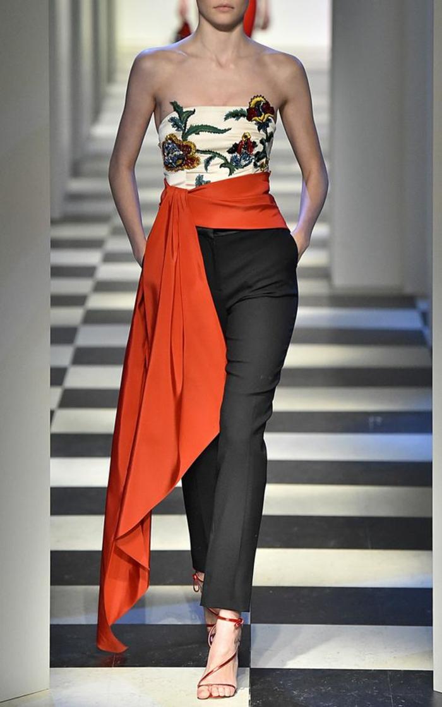 pantalon noir taille haute, longueur aux chevilles, bustier type baroque en blanc avec des ornements broderies en jaune et vert, ceinture sublimée par une large et longue bande de tissu rouge, noué a la taille avec les bouts asymétriques, sandales en rouge et or, tenue pour assister à un mariage