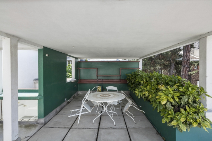 mur végétal intérieur, séparateur d'espace végétal, plantes en vert et jaune, véranda moderne, meubles de jardin en métal blanc, quatre chaises pliantes et une table ronde